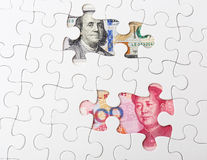 White puzzle with US and chinese banknote Royalty Free Stock Photos