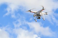 White quadcopter Drone with camera in a blue sky stock photos