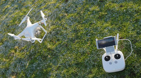 White quadcopter drone with remote controller over a green grass Stock Photos