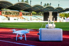 White quadcopter with four motors and propellers standing in large stadium. Drone is ready for take off. White quadcopter with four motors and propellers royalty free stock photo