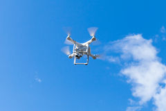 White quadrocopter in blue cloudy sky Stock Images