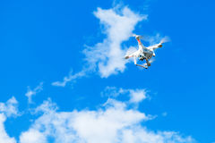 White quadrocopter in blue cloudy sky, drone. Controlled by wireless remote Stock Image