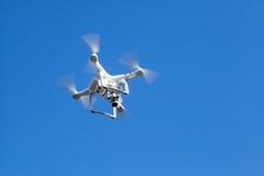 White quadrocopter in blue sky Stock Photo