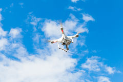 White quadrocopter flying in blue cloudy sky, drone Stock Image