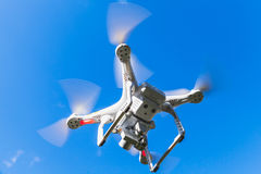 White quadrocopter flying in blue sky, spy drone. White quadrocopter flying in blue sky, drone controlled by wireless remote royalty free stock images