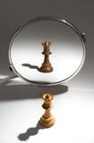 A white queen is looking in a mirror to see herself as a black queen. A  black queen chess piece stands in front of a mirror. The reflection in the mirror shows Stock Image