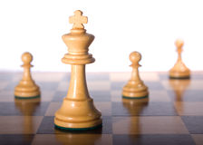 White queen with pawns. Chess piece on a chessboard as a business concept Royalty Free Stock Photography