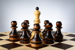 White queen surrounded by black pawns Royalty Free Stock Photography
