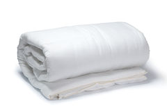 White quilt. Warm and confortable folded white quilt on white background stock image
