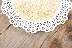 White quinoa on white plate on wooden background Royalty Free Stock Images
