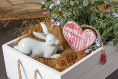 White rabbit and heart in a flower box. Rustic Easter background with a white rabbit ornament and red heart in a white wooden flower box filled with fresh straw Stock Images