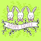 White rabbits with wishes Happy Easter card on green Royalty Free Stock Image