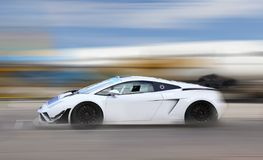 White race car racing on race track. White race car racing at high speed on race track with motion blur royalty free stock photo