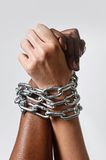White race hand chain locked together with black ethnicity woman multiracial understanding. White Caucasian hand chained with iron chain and locked together with Royalty Free Stock Photo