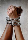 White race hand chain locked together with black ethnicity woman multiracial understanding. White Caucasian hand chained with iron chain and locked together with Royalty Free Stock Images