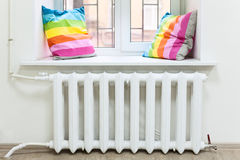White radiator of central heating in domestic room under window. White radiator of central heating is in domestic room under window Royalty Free Stock Photo