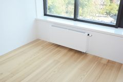 White radiator heating with thermostat for energy saving, wooden. Floor in the modern  room Royalty Free Stock Photos