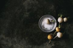 White radish with salt. Whole white fresh organic radish in metal plate with sea salt over dark metal texture background. Top view with copy space. Vegetarian Stock Photography