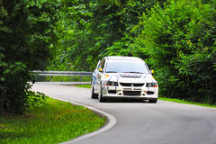 White rally car exiting a curve during a race Stock Photo