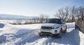 White Range Rover Evoque with a black roof on a winter road on the background of Zhiguli mountains of Samara region. Russia. Clear Sunny day 9 February 2019 royalty free stock photo