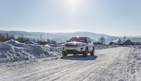 White Range Rover Evoque with a black roof on a winter road on the background of Zhiguli mountains of Samara region. Russia. Clear Sunny day 9 February 2019 stock photography
