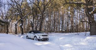 White Range Rover Evoque with a black roof on a winter road in the forest of the Samara region, Russia. Clear Sunny day. 9 February 2019 royalty free stock photos