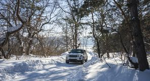 White Range Rover Evoque with a black roof on a winter road in the forest of the Samara region, Russia. Clear Sunny day. 9 February 2019 stock photos