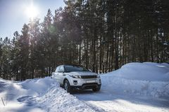 White Range Rover Evoque with a black roof on a winter road in the forest of the Samara region, Russia. Clear Sunny day. 9 February 2019 stock photography
