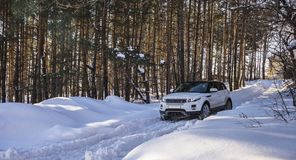White Range Rover Evoque with a black roof on a winter road in the forest of the Samara region, Russia. Clear Sunny day. 9 February 2019 stock photo
