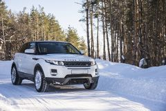 White Range Rover Evoque with a black roof on a winter road in the forest of the Samara region, Russia. Clear Sunny day. 9 February 2019 royalty free stock image