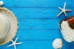 White rattan bag, straw hat on blue background. bamboo trendy bag, starfish, shells. Summer fashion flat lay, vacation, travel stock image