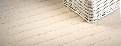 A white rattan box was placed on the beige wool carpet Stock Photo