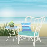 White rattan chair and mosaic table on a deck by the beach Royalty Free Stock Photos