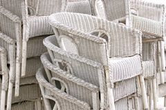 White rattan chairs. Stacked up high at beach restaurant stock photo