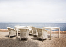 White rattan furniture. In white gravel with horizon view over Mediterranean sea, Mallorca in June Royalty Free Stock Images