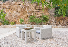 White rattan furniture. In white gravel and tree with yellow flowers in Mallorca in June Royalty Free Stock Photos