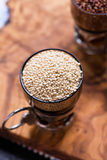 White raw quinoa in a glass cup Royalty Free Stock Images