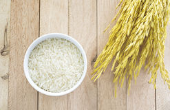 White raw rice and yellow paddy rice on wood background. With soft light fade tone Royalty Free Stock Photography