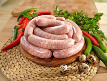White raw sausage on a cutting board. With a quail eggs stock image