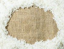 White raw Thai jasmine rice on gunny sack cloth texture Royalty Free Stock Photos