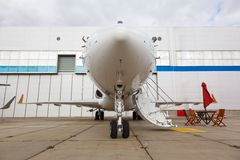 White reactive private jet. The front landing gear and a ladder Stock Images