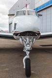 White reactive private jet. The front landing gear on blue sky and clouds Royalty Free Stock Image