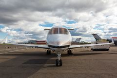 White reactive private jet. The front landing gear and a ladder on blue sky and clouds Royalty Free Stock Photography