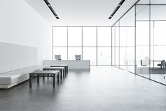 White reception desk in a panoramic office, sofa. White panoramic office lobby with a concrete floor, white and glass walls, a reception and a white sofa near Royalty Free Stock Image