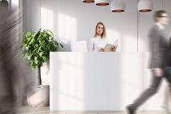 White reception with a door close up, people. Close up of people near a white reception counter is standing in an office with white walls, wooden floor, potted Stock Photography