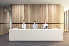 White reception in a wooden office lobby, people. White reception desk standing in a wooden office corridor with a concrete floor. Three businesswomen. 3d Stock Photos