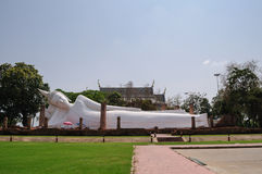 White  reclining Buddha. With temple background Stock Photos
