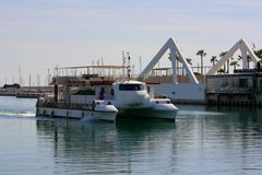 White recreational catamaran returns to the port of Valencia, Spain royalty free stock image