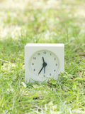 White simple clock on lawn yard, 11:35 eleven thirty five Royalty Free Stock Images