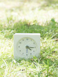 White simple clock on lawn yard, 4:15 four fifteen Royalty Free Stock Photo